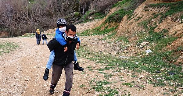 Sırtında taşıyarak okula götürüyor